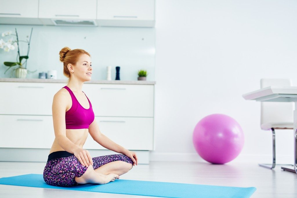 Portrait of fit red haired woman doing yoga exercises at home on floor: sitting with legs crossed in lotus position on mat and smiling