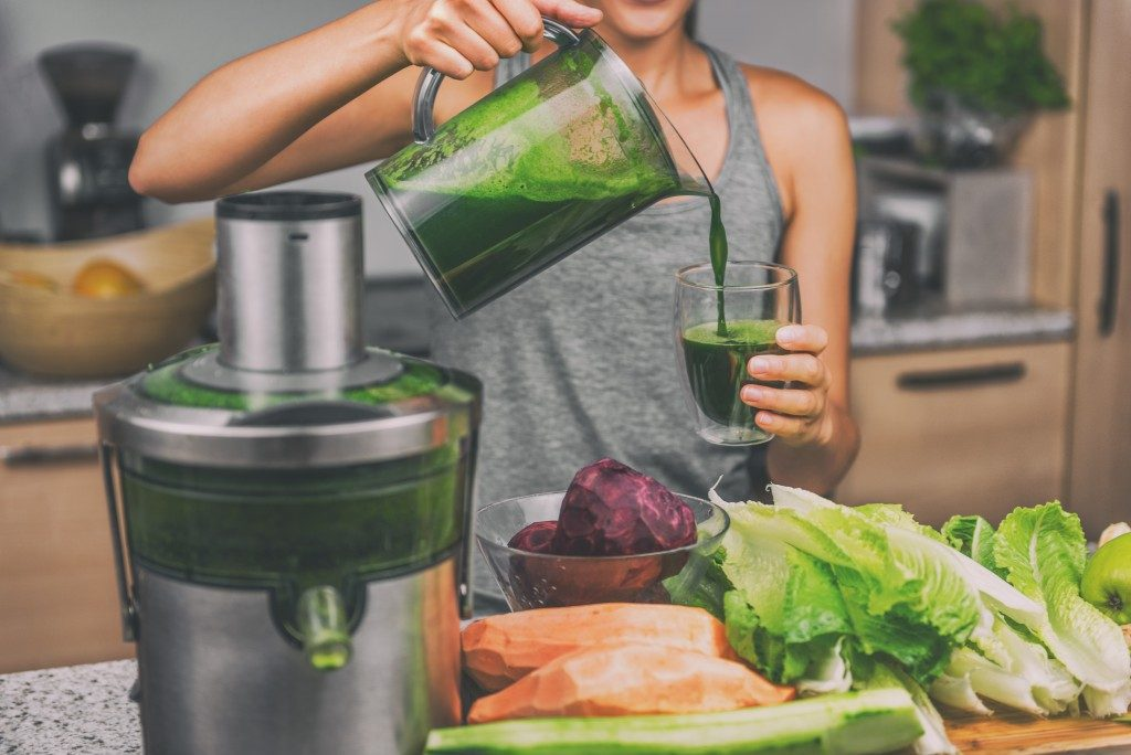 girl pouring her green juice in a glass